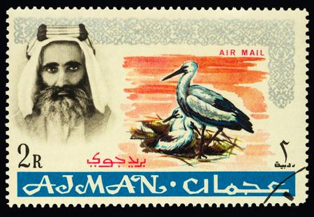 Moscow, Russia - February 05, 2018: A stamp printed in Ajman shows Sheik Rashid and White Stork (Ciconia ciconia), series Native fauna, circa 1965