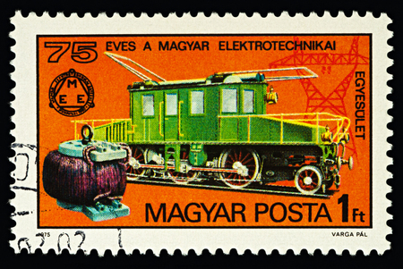Moscow, Russia - February 15, 2018: A stamp printed in Hungary, shows Kando electric locomotive and early transformer, dedicated to the 75th Anniversary of the Hungarian Electrotechnical Union, circa 1975 Éditoriale