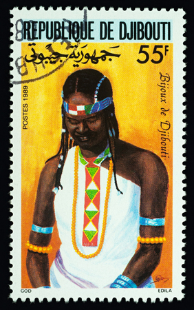 Moscow, Russia - February 23, 2018: A stamp printed in Djibouti shows African girl in dress with traditional ornament, series Traditional Dress, circa 1989