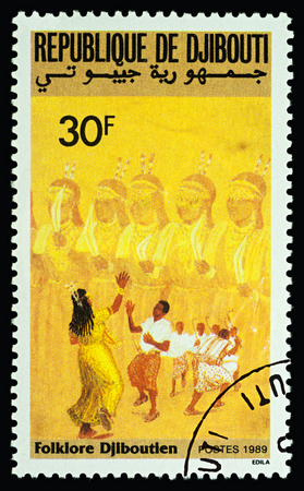 Moscow, Russia - February 23, 2018: A stamp printed in Djibouti shows group of African dancing people, traditional dance, series Folk Dances, circa 1989