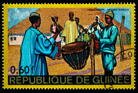 Moscow, Russia - February 28, 2018: A stamp printed in Guinea shows scene of traditional native life in African village, Foulamory, Gaoual Region, series Regional Costumes and Habitations, circa 1968