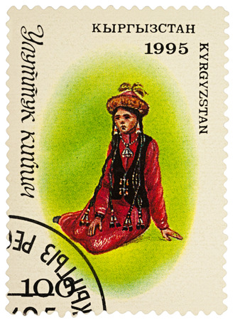 Moscow, Russia - February 25, 2018: A stamp printed in Kyrgyzstan, shows sitting young woman in a traditional Kyrgyz suit, series Traditional Costumes, circa 1995