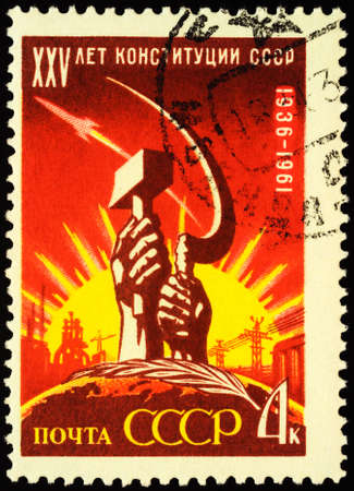Moscow, Russia - April 18, 2020: stamp printed in USSR (Russia), shows hands with sickle and hammer on rising sun background, dedicated to the 25th Anniversary of Soviet Constitution, circa 1961