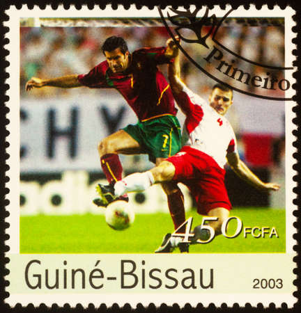 Moscow, Russia - September 21, 2020: stamp printed in Guinea-Bissau shows two football players fight for the ball, series European Football Championship 2004, Portugal, circa 2003