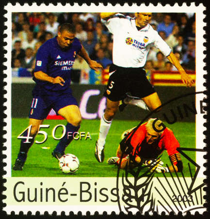 Moscow, Russia - September 21, 2020: stamp printed in Guinea-Bissau shows football players fight for the ball, series Olympic Games - Athens, Greece, circa 2003