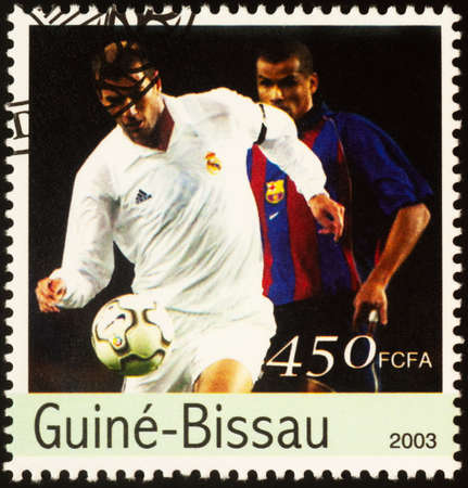 Moscow, Russia - September 21, 2020: stamp printed in Guinea-Bissau shows football player with a ball, series European Football Championship 2004, Portugal, circa 2003
