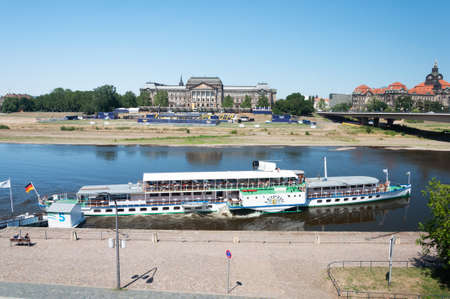 Dresden, Germany- July 26, 2019: Retro river motor ship with tourists departs from the pier on Elbe river