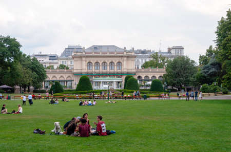 Vienna, Austria - August 02, 2019: people are sitting and resting on green grass, big lawn in Vienna City Park