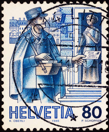 Moscow, Russia - February 01, 2021: stamp printed in Switzerland shows City postman (about 1900), postman hands letter to woman, series Post Delivery, circa 1986