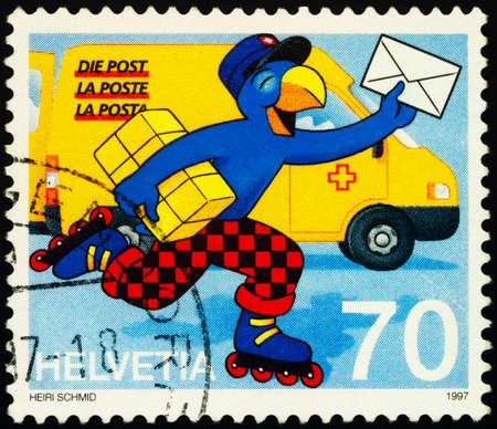 Moscow, Russia - February 01, 2021: stamp printed in Switzerland shows Comic figure Globi as postman, carrying parcel and letter, series 20th International Comics Festival, Sierre, circa 1997