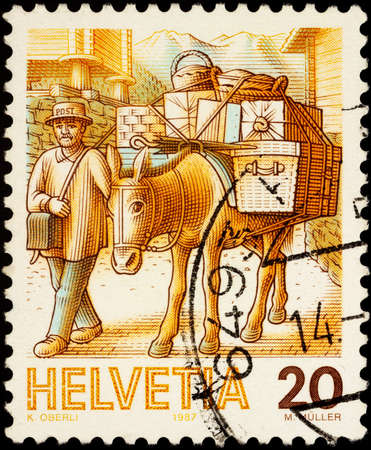 Moscow, Russia - February 03, 2021: stamp printed in Switzerland shows Post by mule, man leads a mule with postal parcels, series Post Delivery, circa 1987 Editorial
