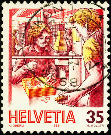 Moscow, Russia - February 03, 2021: stamp printed in Switzerland shows Post office counter, series Post Delivery, circa 1986