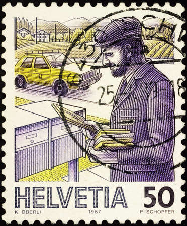 Moscow, Russia - February 03, 2021: stamp printed in Switzerland shows Postman puts letters in mailboxes, series Post Delivery, circa 1987