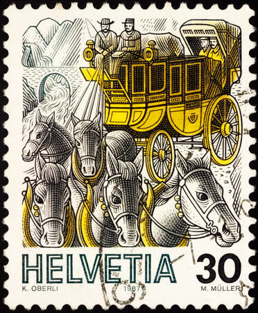 Moscow, Russia - February 04, 2021: stamp printed in Switzerland shows Mail carriage drawn by five horses drives along the road, series Post Delivery, circa 1987 Editorial