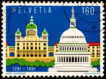 Moscow, Russia - February 23, 2021: stamp printed in Switzerland shows Federal parliament building in Bern and Capitol in Washington, dedicated to the 700th Anniversary of Swiss Confederation, circa 1991