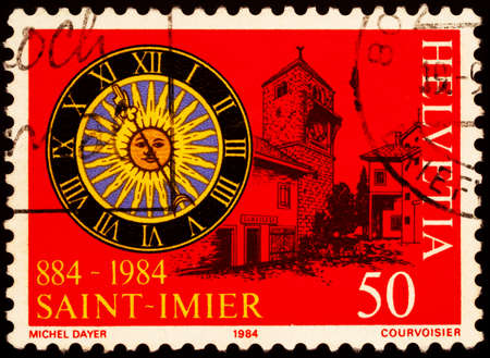Moscow, Russia - February 20, 2021: stamp printed in Switzerland shows Clock face and buildings of Saint-Imier, canton of Bern, Switzerland, dedicated to 1000th Anniversary of Saint-Imier, circa 1984 Editorial
