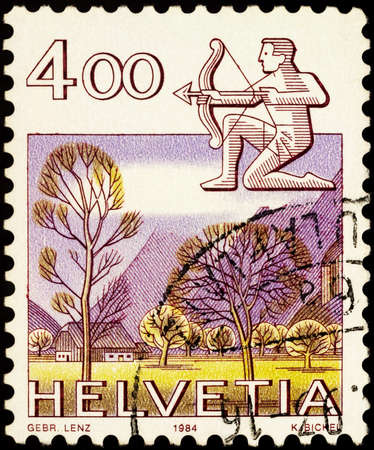 Moscow, Russia - February 22, 2021: stamp printed in Switzerland shows Image of Sagittarius with a bow - sign of zodiac and Glarner landscape, series Zodiac signs and landscapes, circa 1984