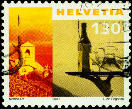 Moscow, Russia - February 24, 2021: stamp printed in Switzerland shows Saint-Saphorin Church and tray with bottle of wine, series Tourism, circa 2000