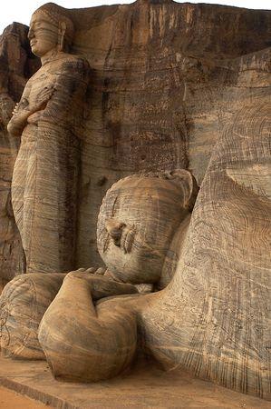obeisance: The reclining Buddha and the chief disciple in Gal Vihare, Polonnaruwa, Sri Lanka. Buddha is reclining and the disciple is standing. Stock Photo