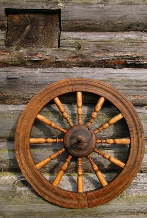 samsara: Hand Spinning Wheel On The Wall Of The Log House Stock Photo