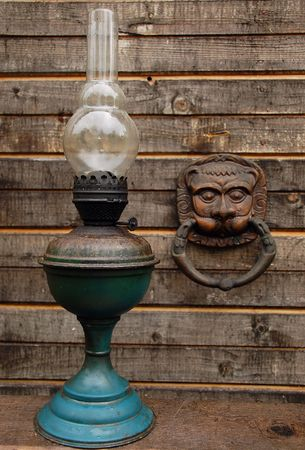 jinn: Betty lamp and door handle looking like a mask in the wooden door background.