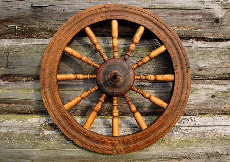 Hand spinning wheel on the wall of the old log house in the Russian village.  Stock Photo