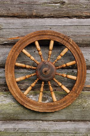 Hand spinning wheel on the wall of the old log house in the Russian village.  photo