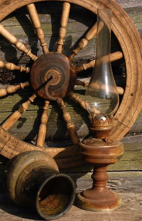 Betty lamp, jug and spinning wheel in the background of the old log-house wall. Stock Photo
