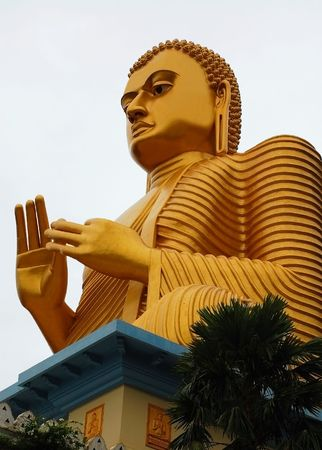 dhamma: The giant golden Buddha statue sitting on the roof of the Golden Temple in Dambulla, Sri Lanka. Built in 2001 it is said to be the largest of its kind in the world. Stock Photo