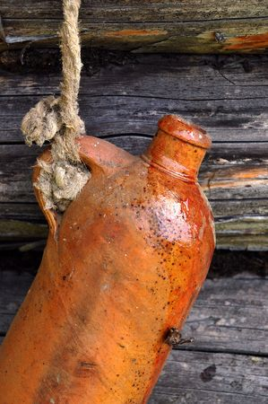 Old ceramic bottle on the wall of the log house. photo