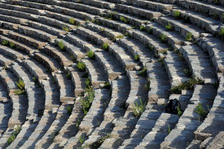 overrun: Rows of Theater in Ephesus, Turkey, overrun with weeds and backpack