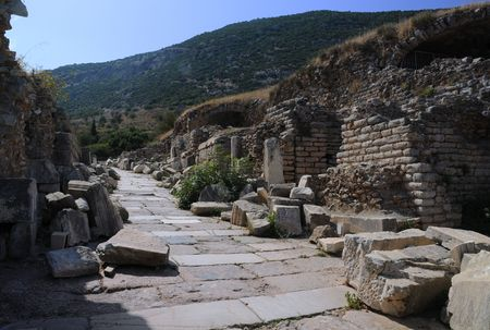 Beginning of Curetes Street in the ancient town of Ephesus in Turkey with residential area on the hill in the background. photo