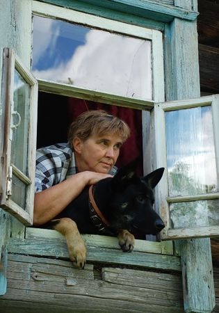 Aged woman and her dog are looking out of the window of her country house in Russia.