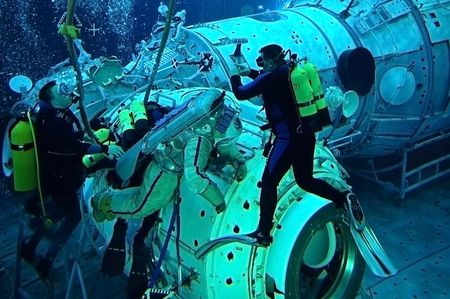 simulate: US astronaut Michael Barratt is training for spacewalks on the exterior of the International space station in the Russian Hydrolab pool in Star City not far away from Moscow. Russian SCUBA divers are assisting Michael to translate in the water. 25 Februar