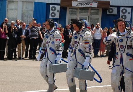 Soyuz spacecraft crewmembers Robert Thirsk (Canada), Roman Romanenko (Russia) and Frank DeWinne (Belgium) are walking to report that the crew is ready for the flight to International Space Station at Baikonur cosmodrome, Kazakhstan, on the 27th of May, 20