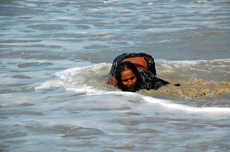 fanaticism: The lady pilgrim is washing her sins in the waters of the Indian ocean. Taken in December 2007 in the state of Goa India. Editorial