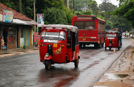 Three-wheelers and the bus on the street in Sri Lanka on a rainy day. Editorial