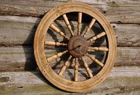 Spinning wheel on the wall  of the house in the Russian village photo