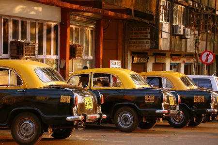 Yellow & black Anbassador cars at the cab-stand in India.