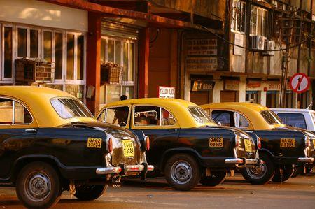 ambassador: Yellow & black Anbassador cars at the cab-stand in India.