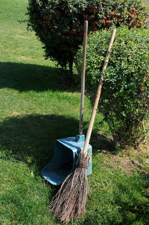 broom handle: Broom and long handle scoop in the park near the bushes on the grass n the summer.