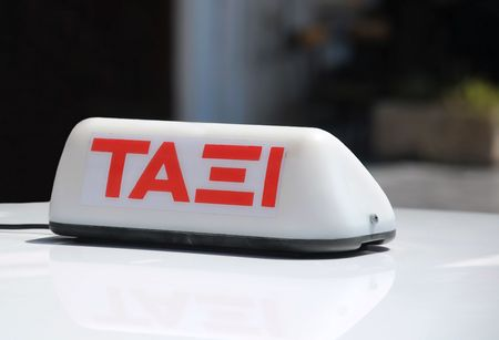 Taxi sign in the Greek language on the roof of the cab in Athens, Greece.