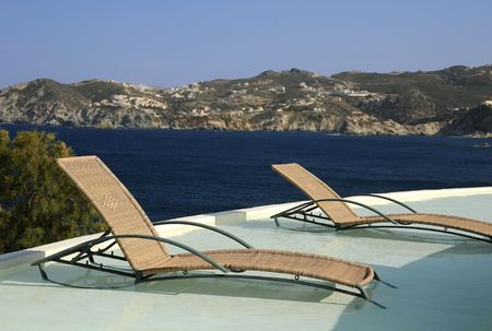 inground: Pools chairs in the water in the hotel recreation area against the background of the  sea and the hill.