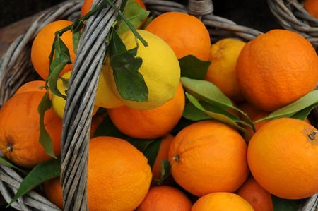 Closeup image of ripe oranges and lemons in the basket.