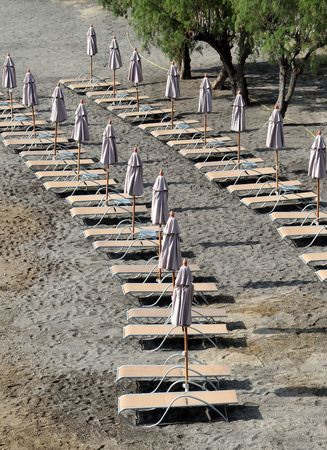 lounges: Folded umbrellas on the empty beach on Crete island in Greece. Stock Photo