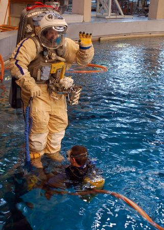 spacesuit: STAR CITY, RUSSIA - FEBRUARY 20: US astronaut J.Williams is taken into water for spacewalk training at Russian Hydrolab water immersion facility Feb 20, 2009 in Star City, Russia. SCUBA diver assists Editorial