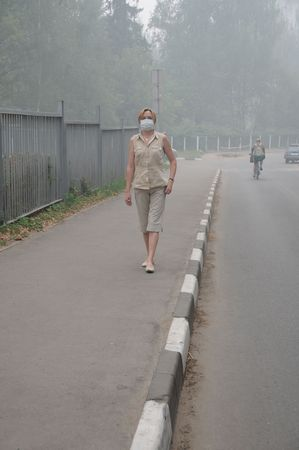 YUBILEINY, MOSCOW REGION, RUSSIA - AUGUST 6: Woman is walking down empty street in thick smog with a mask on her face August 6, 2010 in Yubileiny, Moscow region, Russia. Smog was caused by wildfires