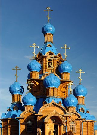 Wooden church with blue domes against blue sky background photo