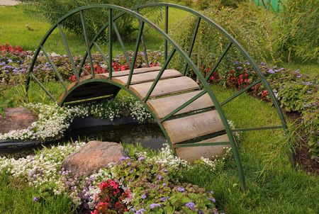 Garden arched bridge, little artificial pond and flowers in the garden