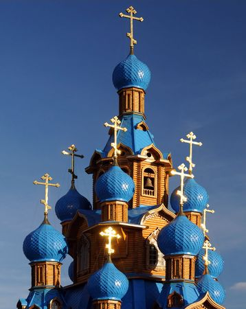 Wooden Orthodox church with blue domes and crosses shining in the sun Stock Photo - 7924985